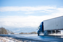 Blue Big Rig Long Haul Semi Truck Transporting Cargo In Refrigerated Semi Trailer Running On Wet Winter Road With Melting Snow