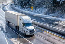 Big Rig White Bonnet Semi Truck With Dry Van Semi Trailer Moving On The Winding Winter Road With Wet Surface And Snow