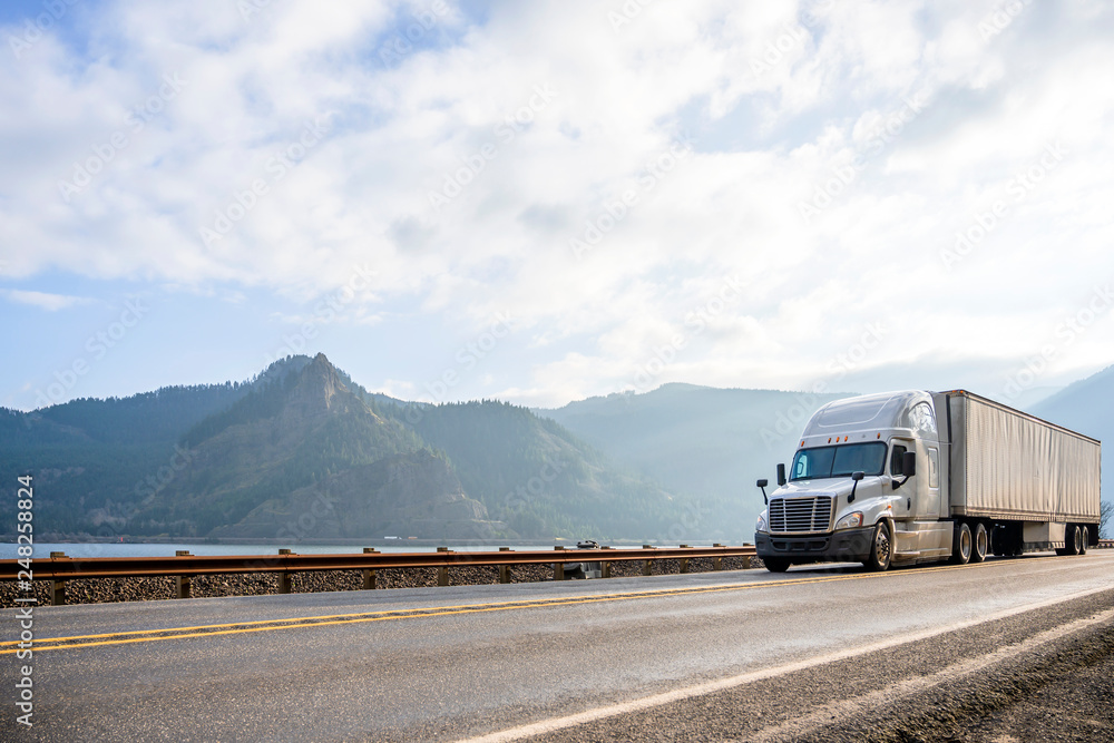Fototapeta Powerful big rig semi truck with dry van semi trailer running with cargo in the road in Columbia Gorge