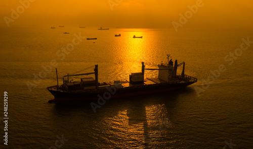 kontenery transportowe sylwetka na morzu i na tle wschodu słońca