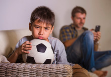Young Sad And Bored Child At Home Couch Feeling Frustrated And Unattended Waiting His Father For Playing Football While Man Networking On Mobile Phone As Internet Addict Father