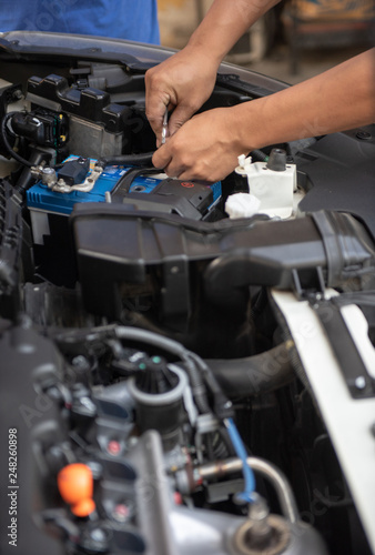 Car Service By An Auto Mechanic In Garage Fixing A Battery With Wrench
