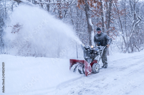 An old white man is using snow blower to plow / blow snow Canvas Print