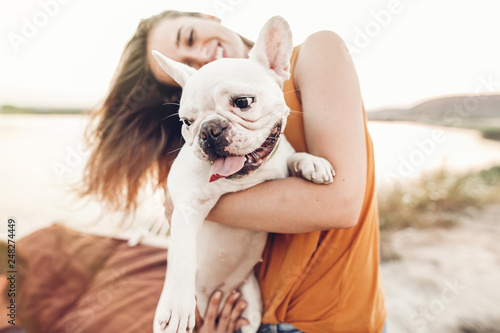 Obraz happy hipster woman playing with bulldog on the beach in sunset light, summer vacation. stylish girl with funny dog resting, hugging and having fun in sun, cute moments. space for text - fototapety do salonu