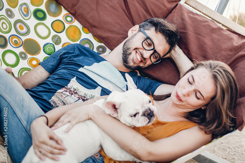 Photo  happy hipster couple with bulldog relaxing in hammock on the beach in sunset light, summer vacation