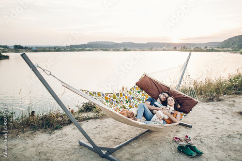 Hipster family on vacation concept, happy woman and man relaxing on a hammock at Poster Mural XXL