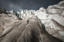 Close-up Crack Is A Deep Blue Crack Found In The Ice Sheet And Black Mud On The Glacier. Wide Angle And Dramatic Sky