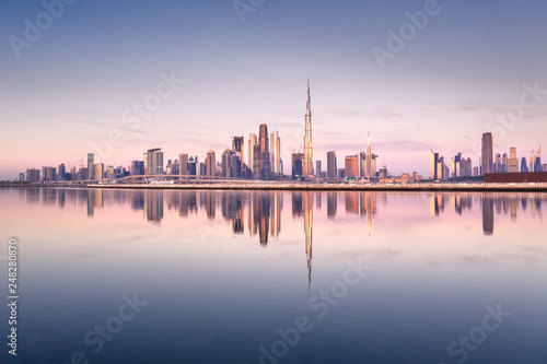 Cuadros en Lienzo Beautiful colorful sunrise lighting up the skyline and the reflection of Dubai Downtown