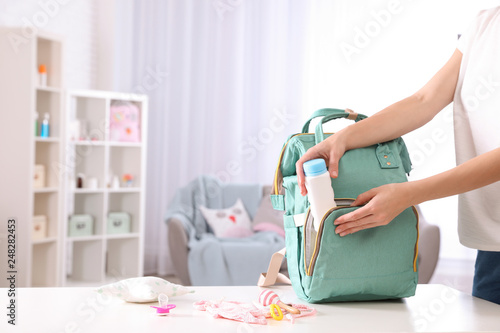 Obraz Woman packing baby accessories into maternity backpack on table indoors, closeup. Space for text - fototapety do salonu