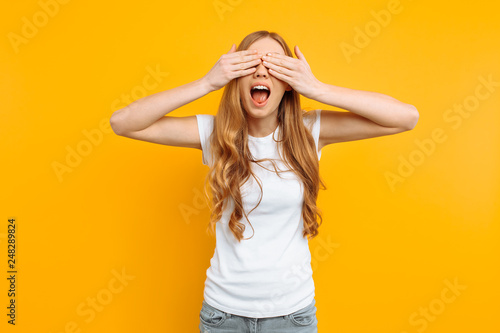 Fotografie, Obraz  beautiful girl closes her eyes with her hands, on a yellow background, playing h