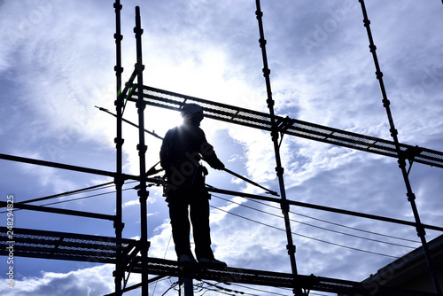 Fototapeta A building worker steeplejack assembling the scaffold at the housing construct