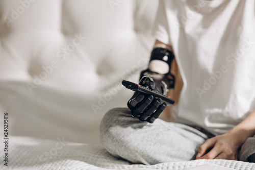 Fotografie, Obraz  young girl with an artificial arm pressing the buttons on the remote control, development of medicine