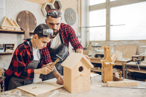 Fototapeta Carpenter building a wooden birdhouse together with his kid