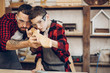 Fatherhood, hobby, carpentry, woodwork and people concept - Father and little son wearing protective glasses testing hand-made wood sword smooth surface at workshop