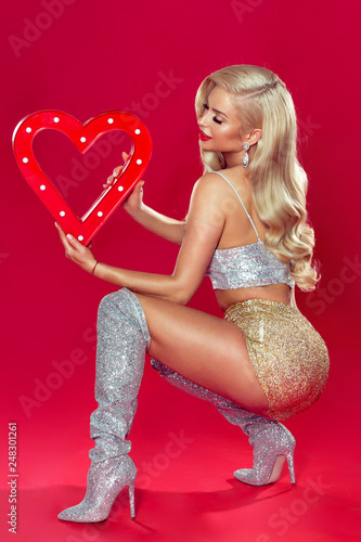 Fotografie, Obraz  Sexy blonde woman in shiny lingerie holding big heart