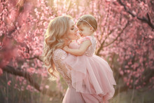 Portrait Of Young Beautiful Mother With Her Little Girl. Close Up Still Of Loving Family. Attractive Woman Holding Her Child In Pink Flowers And Smiling
