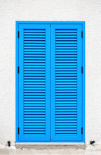 A Window With Blue Shutters On A White Wall
