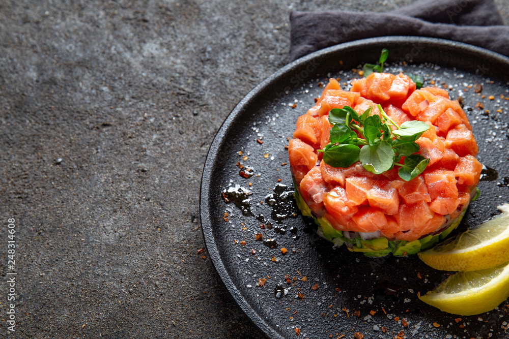 Fototapety, obrazy: Raw salmon, avocado purple onion salad served in culinary ring on black plate. Black concrete background