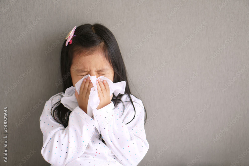 Fototapety, obrazy: Asian child or kid girl sick with sneezing on nose and cold cough on tissue paper because weak or virus and bacteria from dust weather and kindergarten and pre school for medical background gray space