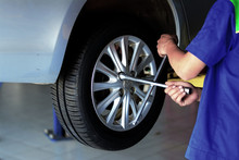 The Mechanic In Blue Uniform Using Cross Wrench Tighten The Bolts Wheel