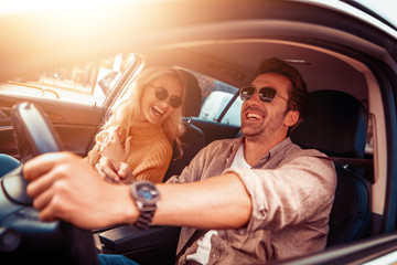 Happy couple in car on road trip smiling at each other