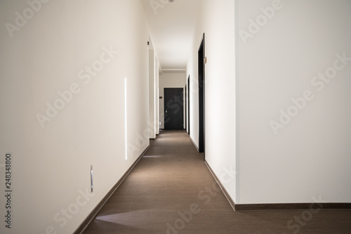 Foto white hotel hallway with many doors and lights