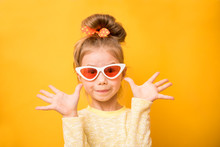 Surprised Funny Little Girl In Sunglasses Holding Hands Raised And Looking Camera Over Yellow