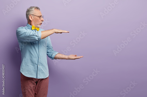 Fotomural  Sideways shot of handsome grey haired man shapes big object with two hands, gasp