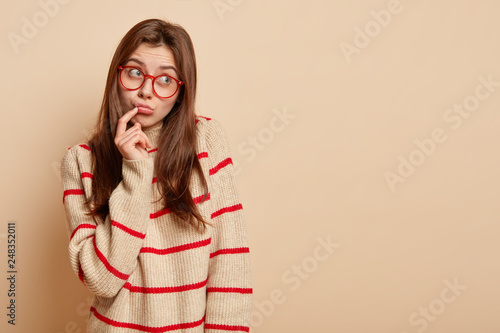 Fotografija  Thoughtful Caucasian dark haired woman looks aside, wears transparent glasses and casual jumper, poses over beige background with copy space for your promotional content or advert