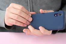 Caucasian Man In A Gray Sweater Puts On A New Case On Mobile Phone With Selective Focus. White Male Hands Are Holding A Smartphone And Putting On A Blue Cover. Silicone Case For Digital Gadget