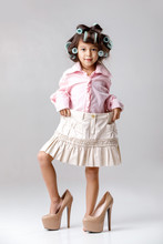 Cute Little Child Girl In Hair Curlers Playing With Her Mother's Clothes And Shoes