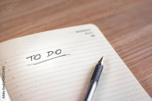 Photo  To do list being hand written in a notebook with lines