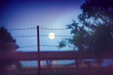 Barbed Wire Fence At The Countryside Ranch Under The Moon Light, Summer Night