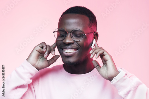 Studio shot of young african man listening to music with wireless earphones isolated on pink background - 248355497