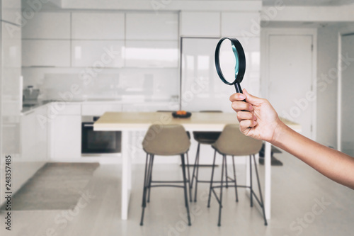 Foto Home inspection - magnifying glass inspector looking at kitchen house background