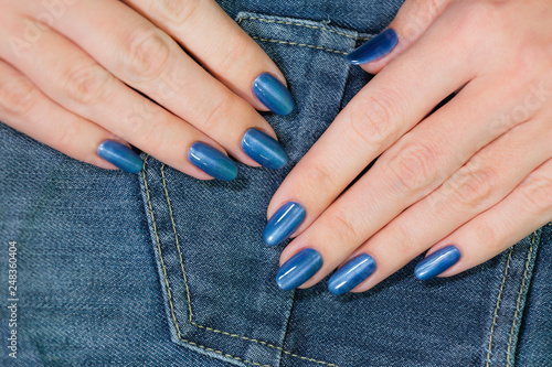 Fotografía  Closeup view of beautiful female hands with blue glossy professional manicure isolated on denim jeans texture