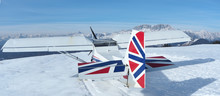 Monte Pora, Bergamo, Italy. A Single Engined, General Aviation Light Aircraft Parked On A Snow Covered Plateau. UK Flag Colors As Livery