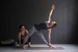 Yoga class instructor and beginner making asana exercises.