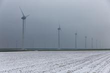 Dutch Rural Landscape With Wind Turbines In Winter Haze