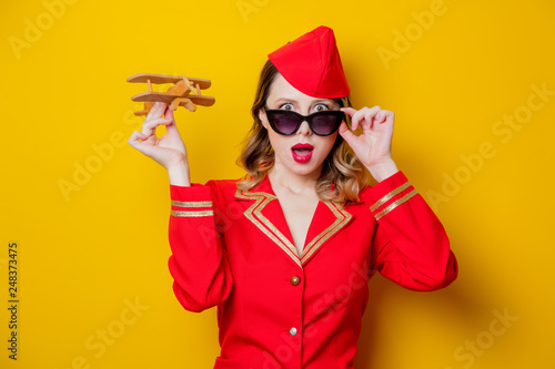 Photo charming vintage stewardess wearing in red uniform with airplane