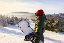 Girl Snowboarder Stands With Snowboard On Mountain's Top. Ski Resort