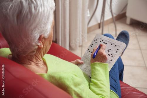 Photo donna anziana fa le parole crociate seduta sul divano
