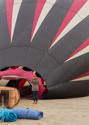 Fotografie, Obraz  A woman in warm winter clothes watches as a red white and black hot air balloon fills in preparation for lift off