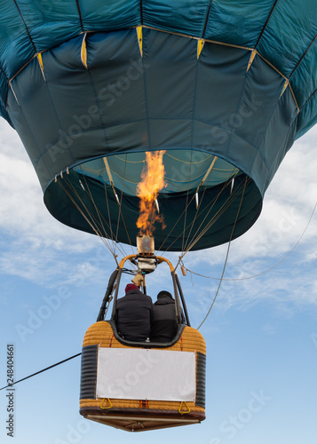 Fotografie, Obraz  Two people ride in the basket of a hot air balloon as the flame from the burner heats the air inside