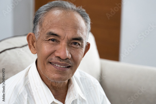 Fotografía asian senior oldman sitting on the sofa smile when look at the camera