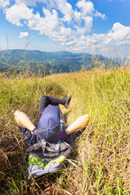 Young Traveler Lie Down In The Grass Field Taking Resting During Hiking.
