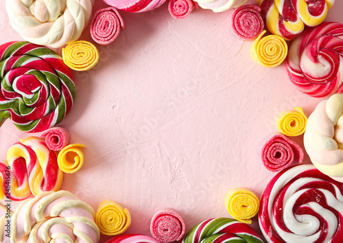 Frame made of different sweets on color background