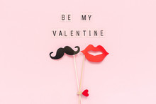 Text Be My Valentine And Couple Paper Mustache, Lips Props Fastened Clothespin Heart On Stick On Pink Paper Background. Concept Valentine's Day, Valentine Card Top-down Composition Creative Flat Lay