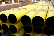 Gas Yellow Pipes And Coil Stacked On Pallet At Construction Road Works