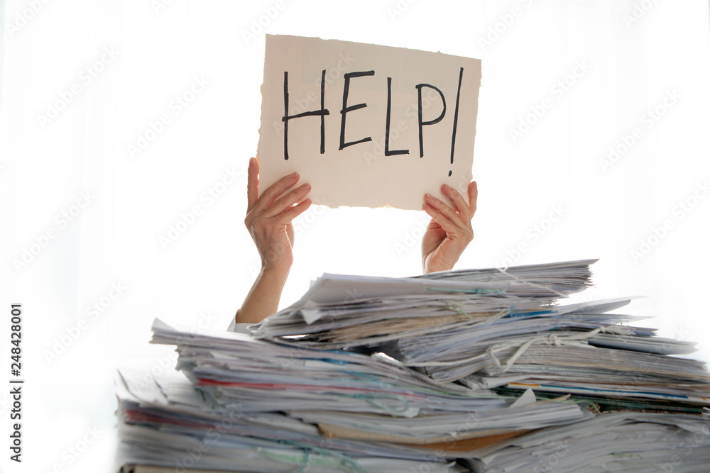 Fototapeta Person under a pile of papers with a hand holding a sign of help. Accounting.